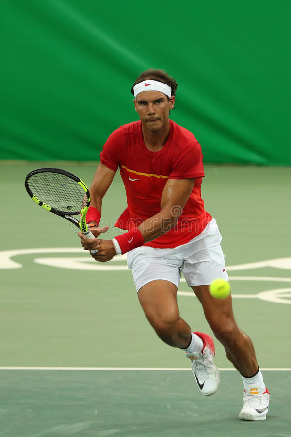 Le champion olympique Rafael Nadal de l'Espagne dans l'action pendant le ` s des hommes choisit le premier match de rond de Rio 2 photographie stock
