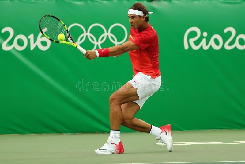 Le champion olympique Rafael Nadal de l'Espagne dans l'action pendant le ` s des hommes choisit le premier match de rond de Rio 2 photo libre de droits