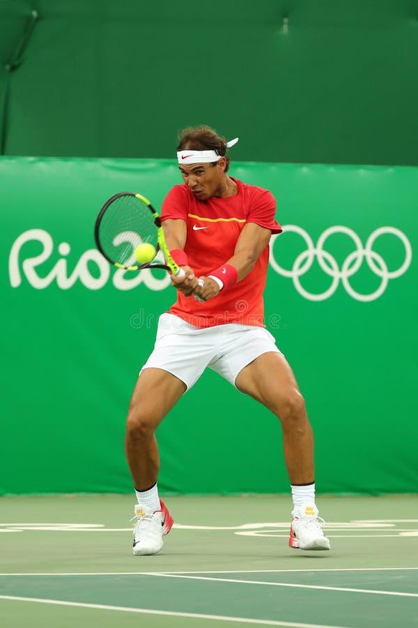 Le champion olympique Rafael Nadal de l'Espagne dans l'action pendant les hommes choisit le premier match de rond de Rio 2016 Jeu photo stock