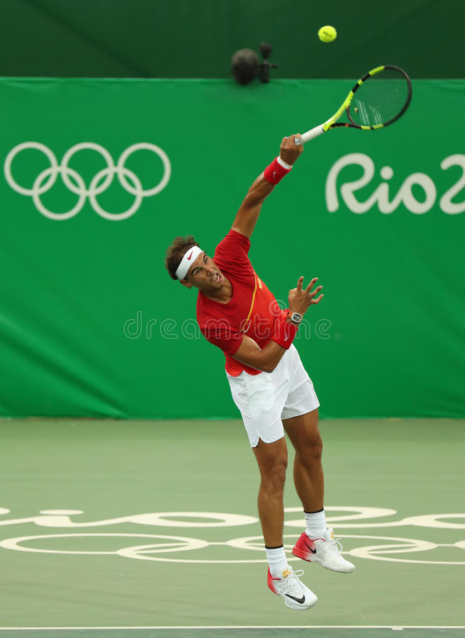 Le champion olympique Rafael Nadal de l'Espagne dans l'action pendant les hommes choisit le premier match de rond de Rio 2016 Jeu image stock