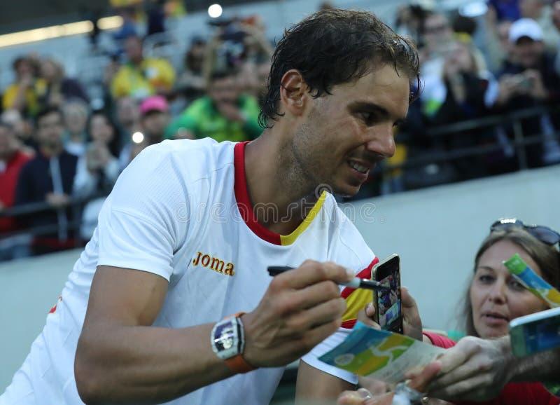 Le champion olympique Rafael Nadal de l'Espagne donne des autographes après que le ` s d'hommes choisisse la demi-finale de Rio 2 photos stock