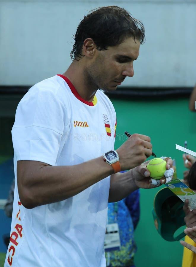 Le champion olympique Rafael Nadal de l'Espagne donne des autographes après que le ` s d'hommes choisisse la demi-finale de Rio 2 photo stock
