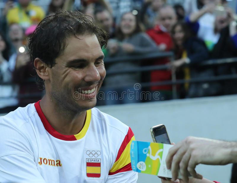 Le champion olympique Rafael Nadal de l'Espagne donne des autographes après que le ` s d'hommes choisisse la demi-finale de Rio 2 photo libre de droits