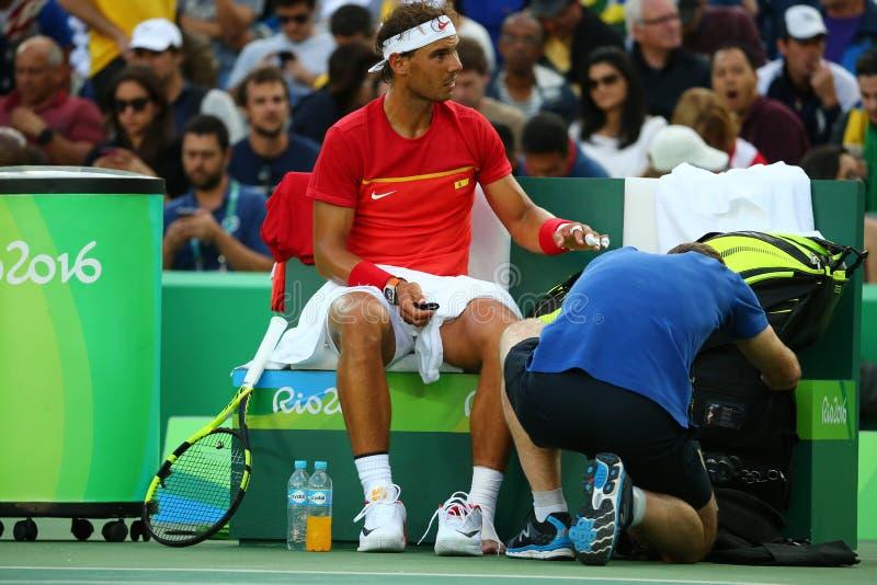 Le champion olympique Rafael Nadal de l'Espagne recevant l'aide médicale pendant choisit des quarts de finale de Rio 2016 Jeux Ol photos libres de droits