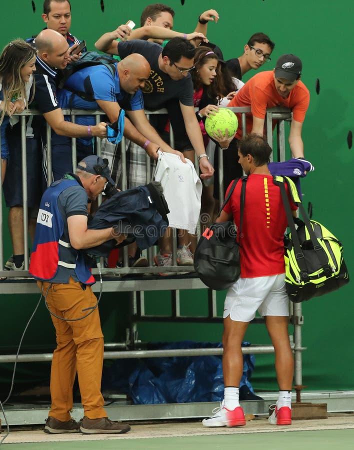Le champion olympique Rafael Nadal de l'Espagne signe des autographes après que le ` s d'hommes choisisse le premier match de ron images libres de droits