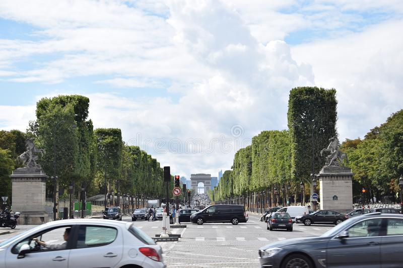 Le champs elysee and Arch of Triumph Paris France. Perspective of le champs elysee and the Arch de Triomphe in rush hour. Paris France stock photos