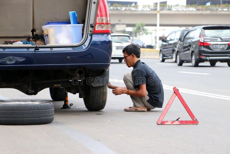 Le changement d'homme les pneus seul près de la route au centre de Jakarta images libres de droits