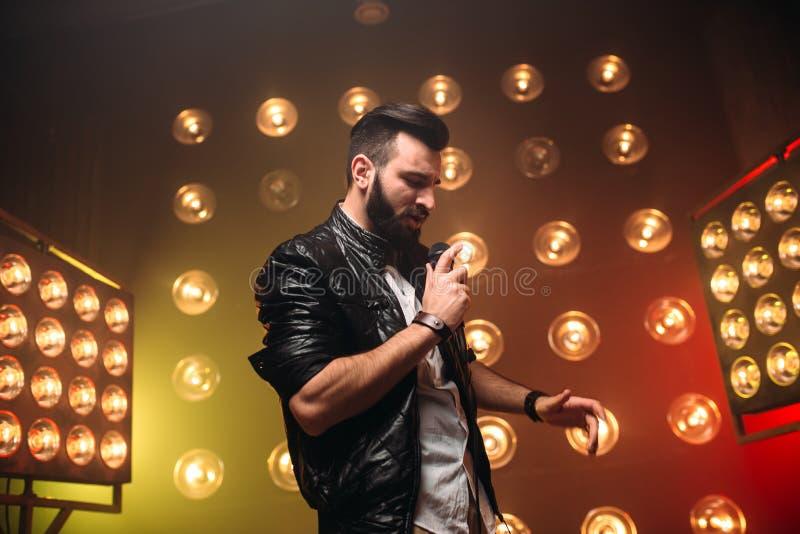 Le chanteur barbu brutal avec le microphone chantent une chanson image stock
