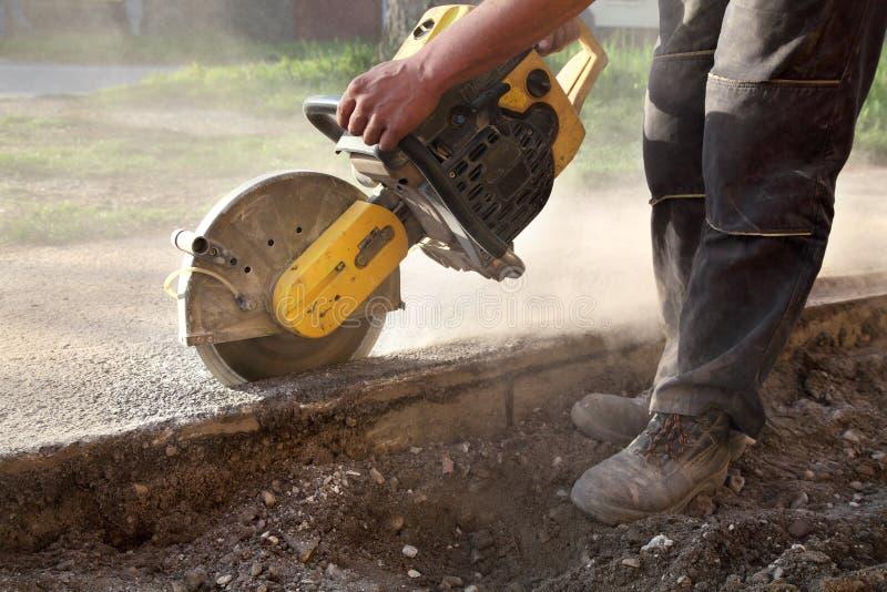 Le chantier de construction, asphalte de coupe de travailleur avec scie le péage de lame photographie stock