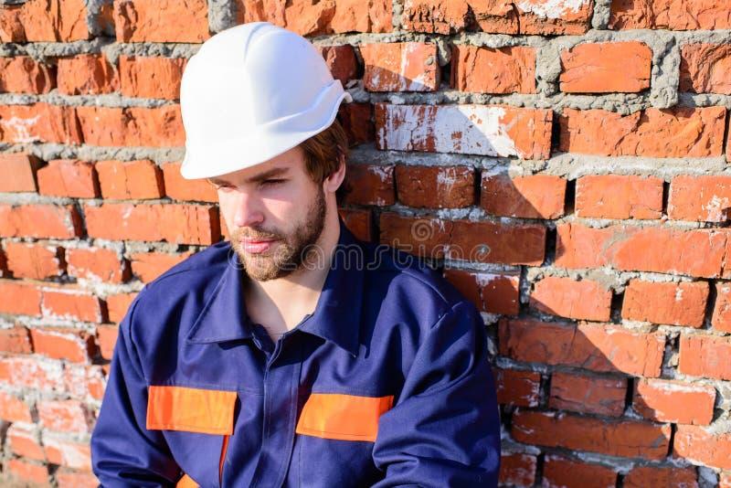 Le chantier de construction de casque de constructeur reposent le mur de briques maigre de détente Constructeur beau barbu de cas images libres de droits