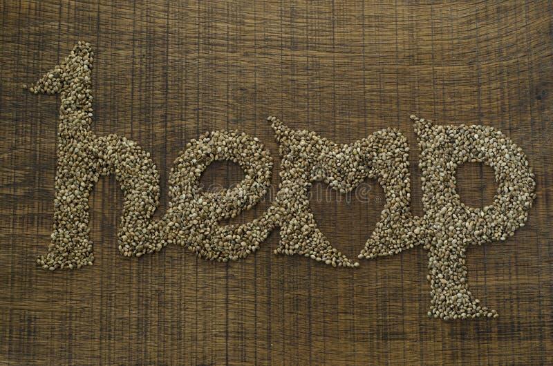Le chanvre de mot écrit artistiquement en graines de chanvre sur un cho en bois photos stock