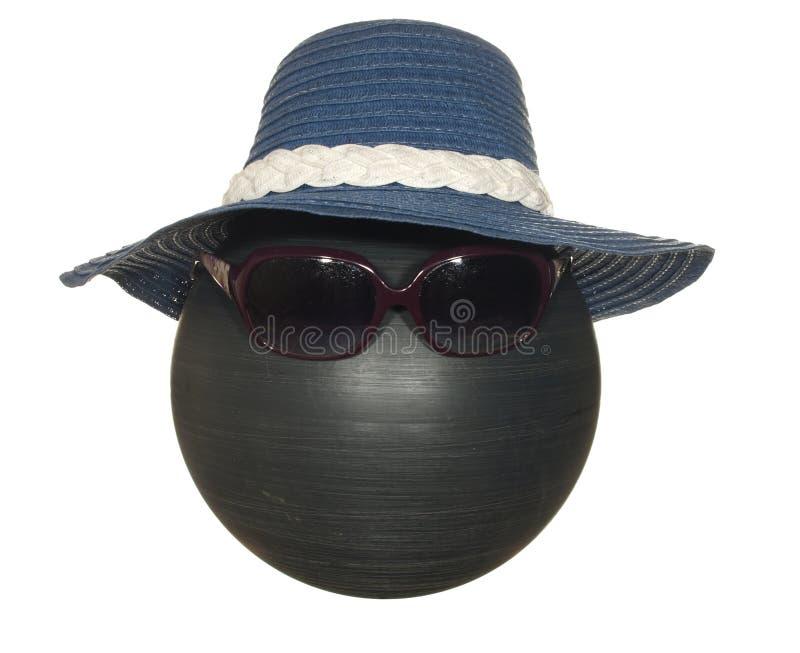 Le chapeau bleu de Madame avec un ruban blanc et les lunettes foncées sur une boule en plastique noire d'isolement sur un fond bl photo stock