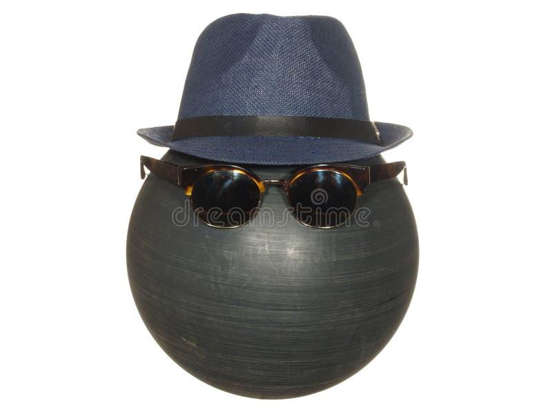 Le chapeau bleu et les lunettes foncées des hommes sur une boule en plastique noire d'isolement sur le fond blanc photo libre de droits