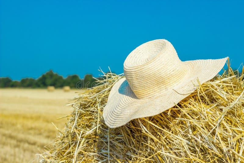 Le chapeau d'un agriculteur seul sur une meule de foin dans le domaine après un dur labeur photo stock