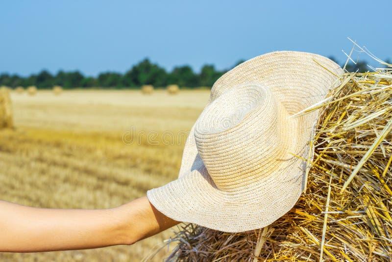 Le chapeau d'un agriculteur seul sur une meule de foin dans le domaine après un dur labeur photos stock