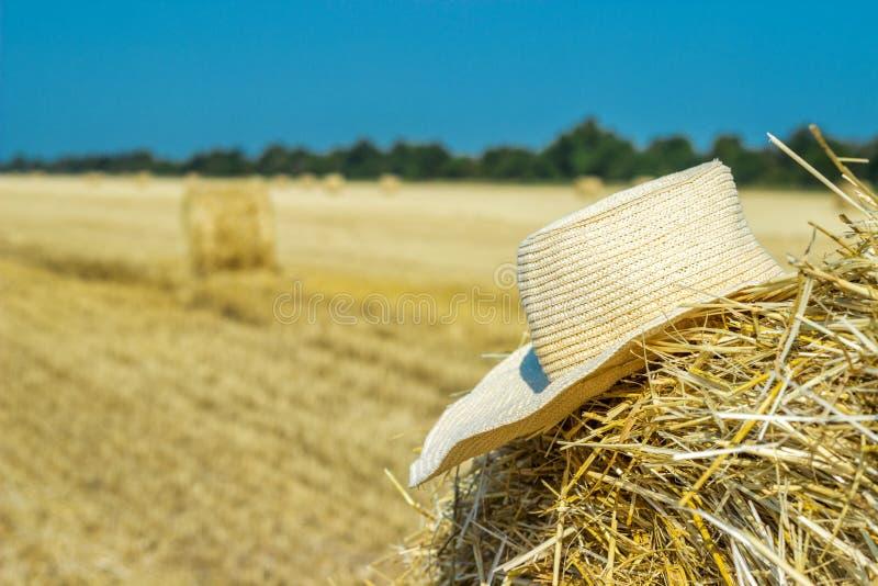 Le chapeau d'un agriculteur seul sur une meule de foin dans le domaine après un dur labeur images stock