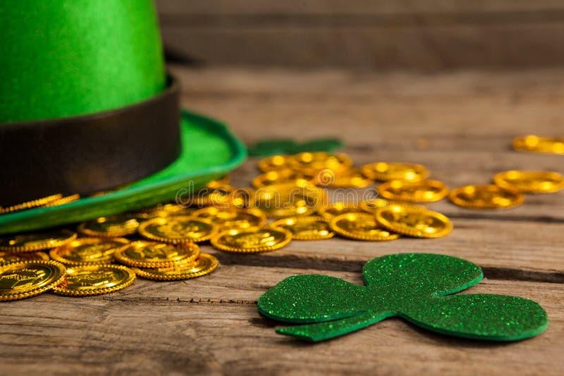 Le chapeau de lutin de jour de St Patricks avec du chocolat d'oxalide petite oseille et d'or inventent photo stock