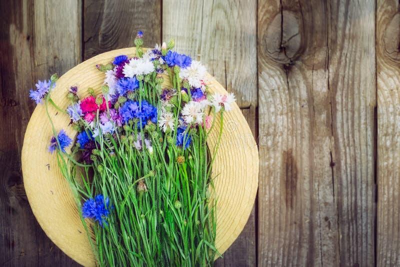 Le chapeau de paille et la sauvage-fleur romantique de colorfull lient le bouquet sur le fond rustique en bois Disposition de vin photographie stock libre de droits