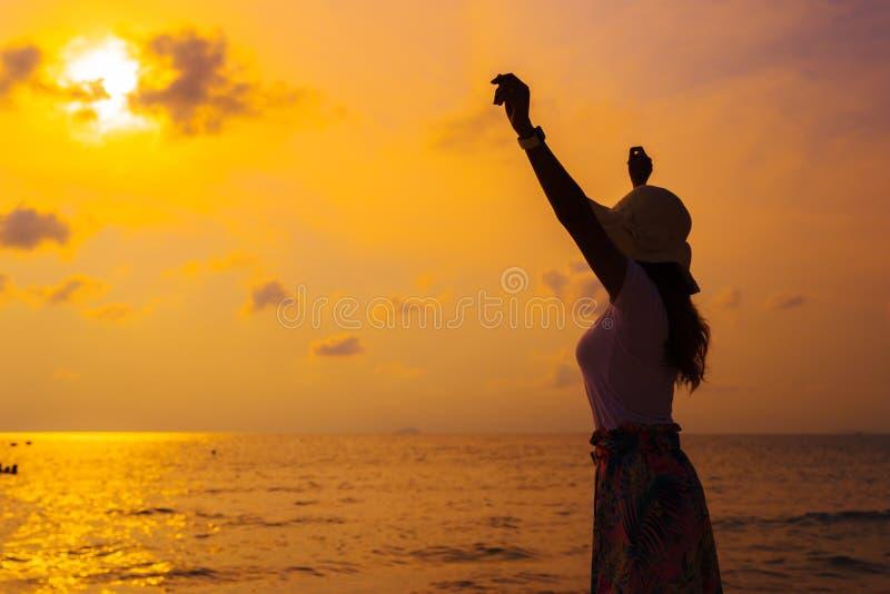 Le chapeau de port de femme avec des bras a soulevé la position sur la plage de mer au coucher du soleil photos libres de droits