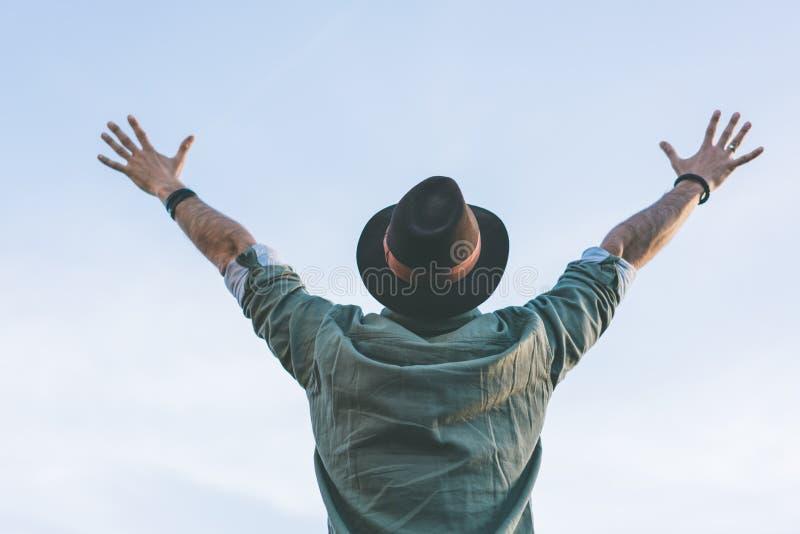 Le chapeau de port masculin de mode de hippie, appréciant la vue du ciel bleu et clair avec a soulevé ses mains  images libres de droits