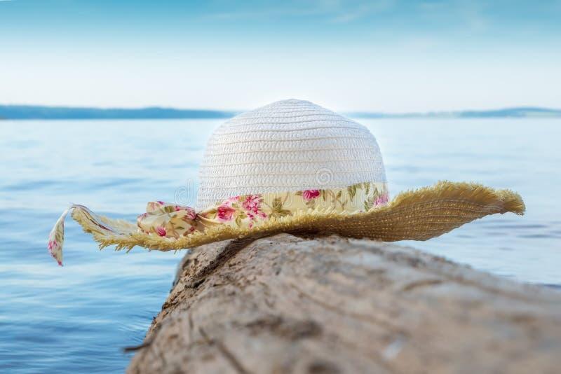 Le chapeau des femmes sur une ouverture le fond de l'eau bleue et du ciel photos libres de droits