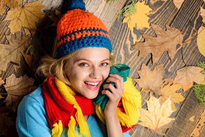 Le chapeau et l'écharpe tricotés par femme de hippie tiennent des feuilles d'automne Configuration gaie de visage de fille sur le photo stock