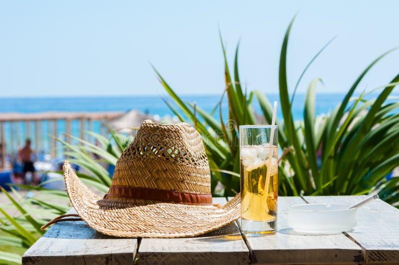 Le chapeau a mis dessus la table à côté d'un verre de libre du Cuba images libres de droits