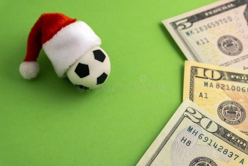 Le chapeau rouge de Santa Claus est habillé sur un ballon de football de souvenir à côté des dollars sur un fond vert Pari de spo photos libres de droits