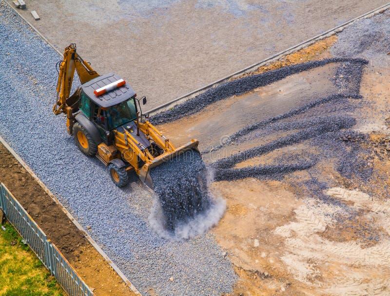 Le chargeur avant a versé le gravier de la poche au chantier de construction du stade d'école images stock