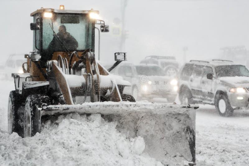 Le chargeur de roue d'embout avant enlève la neige de la route pendant la tempête d'hiver de chute de neige importante, visibilit photos libres de droits