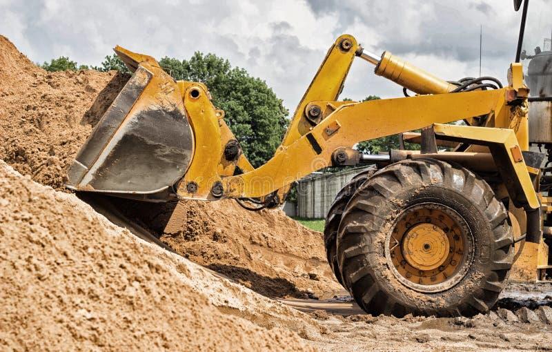 Le chargeur jaune de tracteur prend un seau de la terre, mécanique, poche avec la terre photographie stock