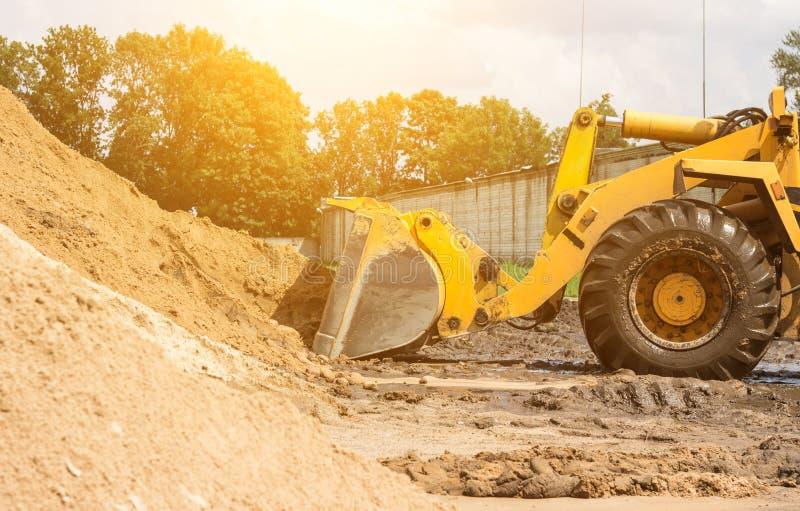Le chargeur jaune de tracteur prend un seau de la terre, mécanique, de poche avec la terre et de soleil photographie stock libre de droits