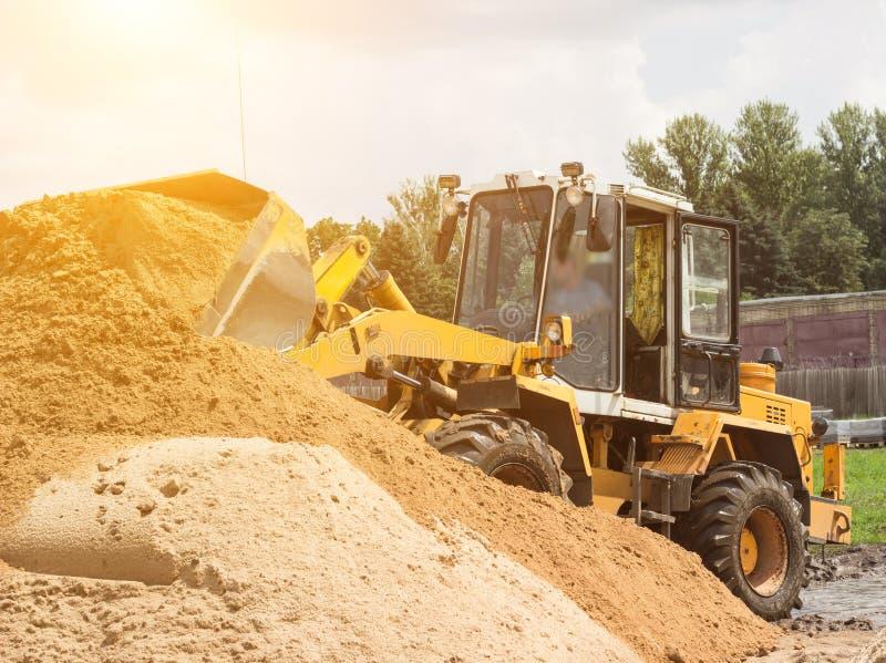 Le chargeur jaune de tracteur prend un seau de la terre, mécanique, de poche avec la terre et de soleil images libres de droits