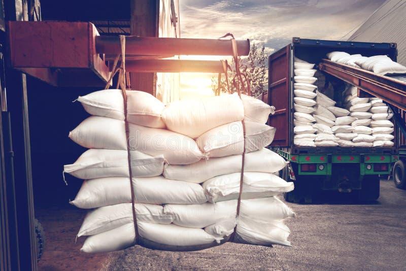 Le chariot élévateur manipulant le sucre blanc met en sac le bourrage dans un camion de récipient image libre de droits