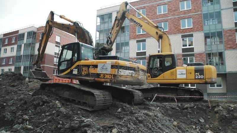 Le chariot au ralenti a tiré deux noirs et excavatrices jaunes au chantier banque de vidéos