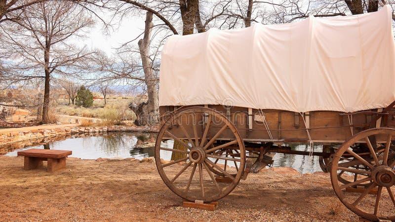 Le chariot couvert se repose à côté de l'eau de source naturelle images libres de droits