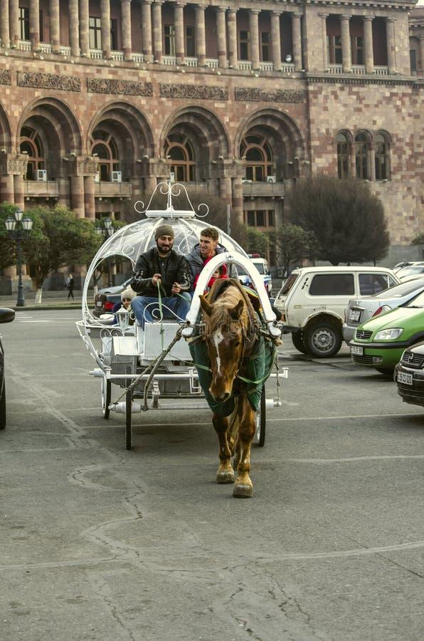 Le chariot original blanc tiré par un rouge avec le cheval blanc de cirque de taches porte des personnes avec des enfants autour  photo stock