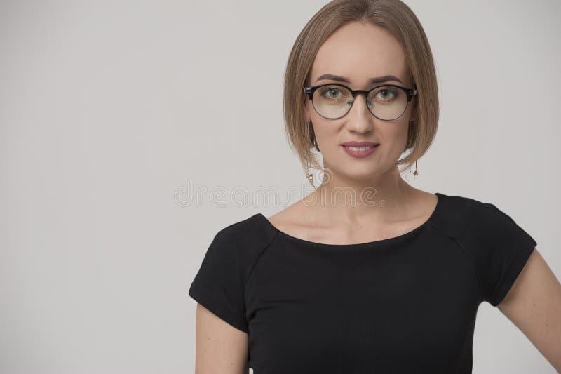 Le charma den unga affärskvinnan som bär den formella dräkten och stilfulla exponeringsglas royaltyfri fotografi