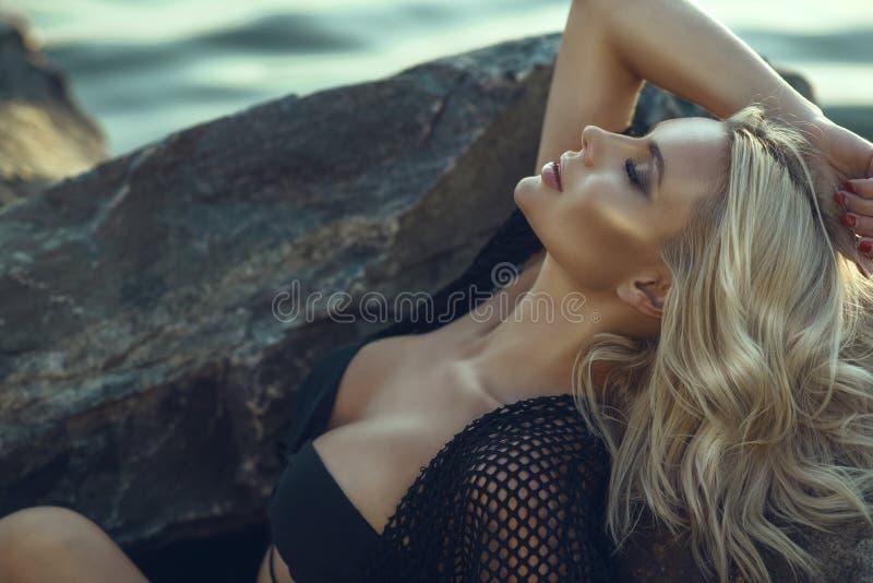 Le charme magnifique a bronzé la femme blonde avec les yeux fermés portant la tunique noire de maillot de bain et d'été détendant photos libres de droits