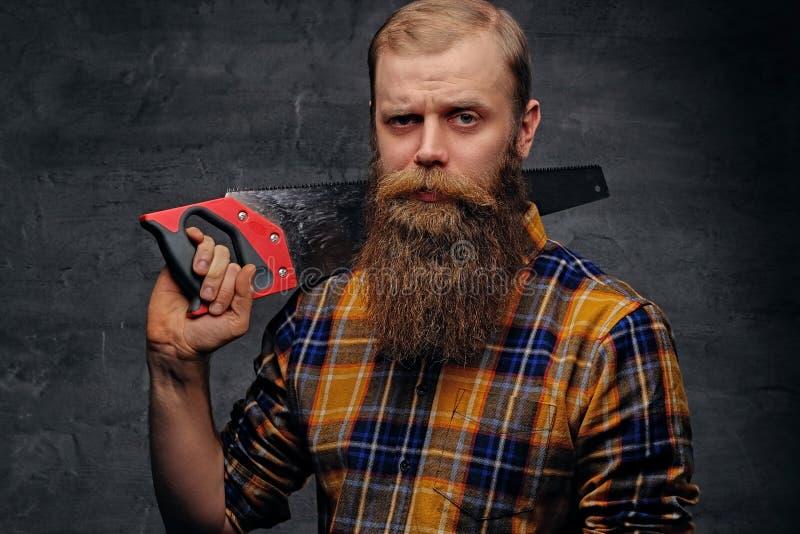 Le charpentier barbu s'est habillé dans une chemise de plaid tient la scie à main photo libre de droits