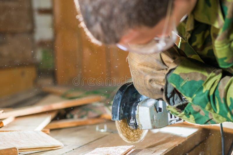 Le charpentier dans les lunettes traite la surface des conseils photographie stock