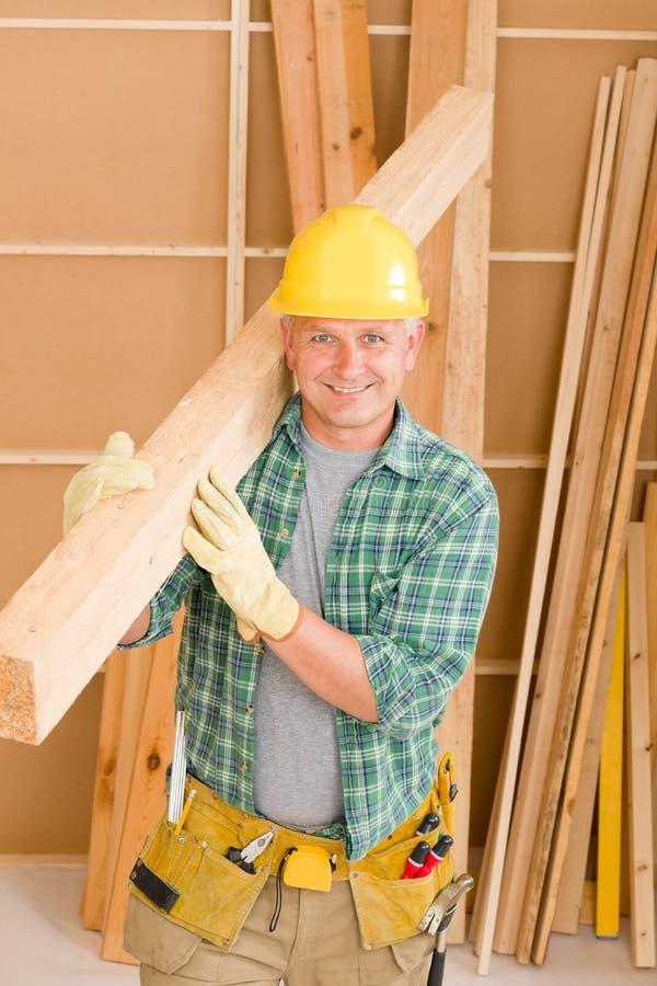 Le charpentier de bricoleur mûr portent le faisceau en bois photographie stock libre de droits