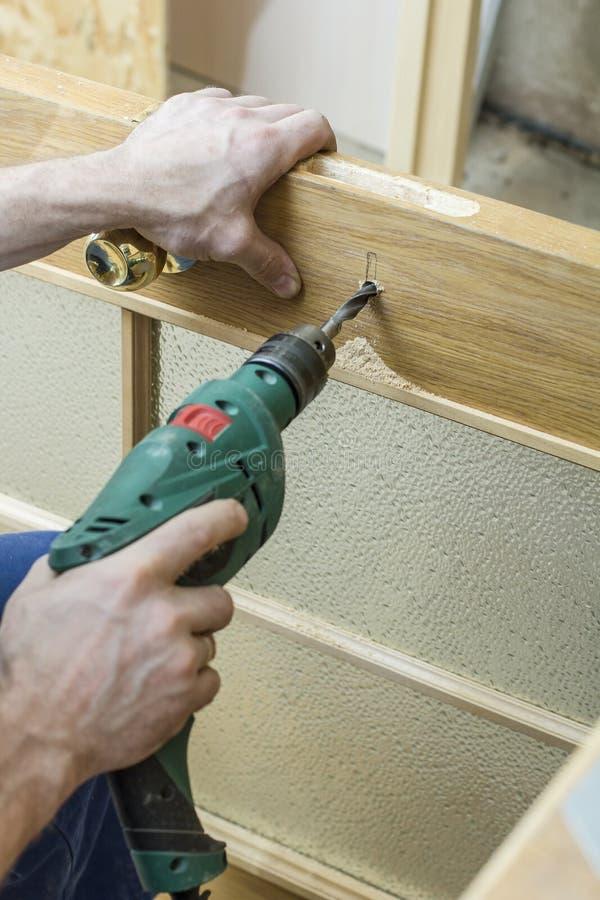 Le charpentier fait à un trou dans une porte en bois la serrure de mortaise pour par image stock