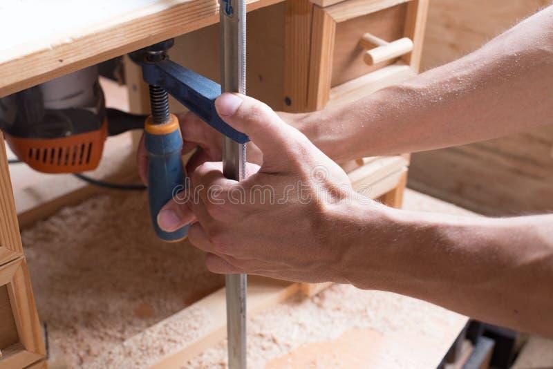 Le charpentier fait main et de métier de meubles de concept s'est engagé en traitant le bois dans son atelier Mains d'homme fonct images stock