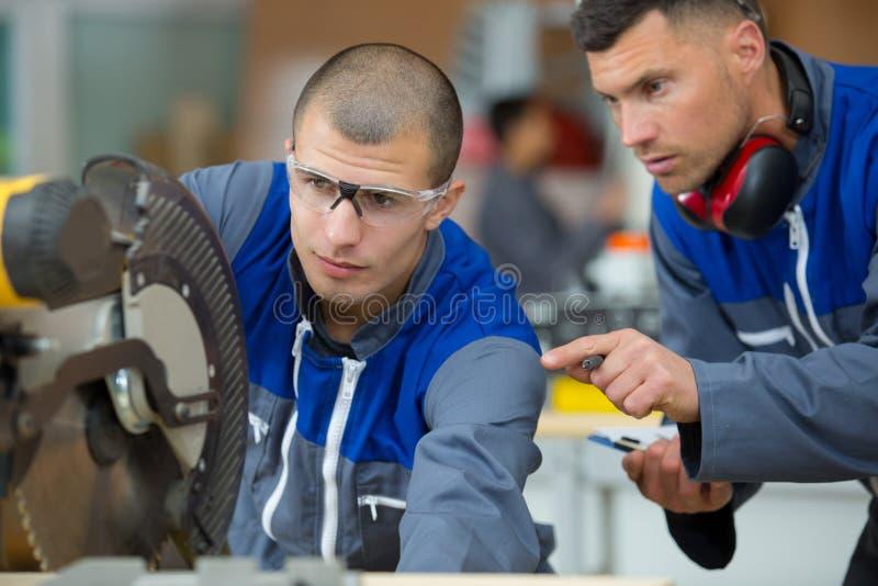 Le charpentier industriel de travailleur de la construction employant la circulaire a vu image stock
