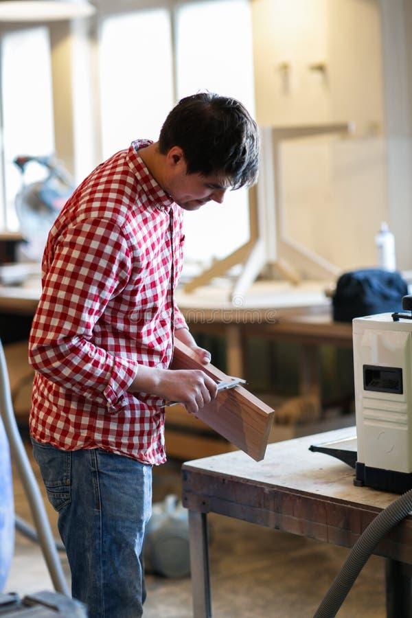 Le charpentier mesure l'épaisseur de conseil des calibres, joiner photographie stock libre de droits
