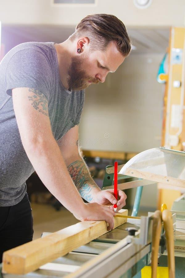 Le charpentier mesure la longueur d'une planche en bois avant de scier images libres de droits