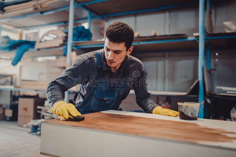 Le charpentier peint un bois avec la laque photographie stock