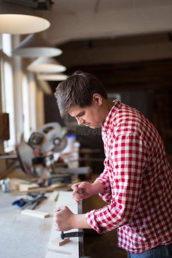 Le charpentier travaillant avec les planches en bois, remettent le vice, le concept d'a photos libres de droits