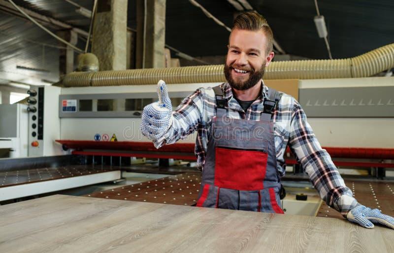 Le charpentier travaille à la planche en bois dans l'atelier de menuiserie photos stock